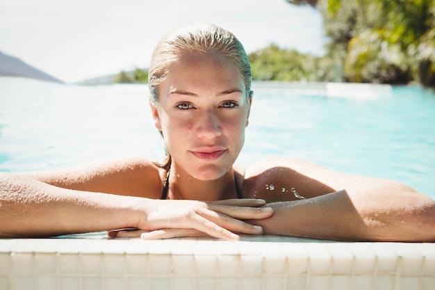 Porträt der schönen blondine im pool, das am rand sich lehnt Premium Fotos