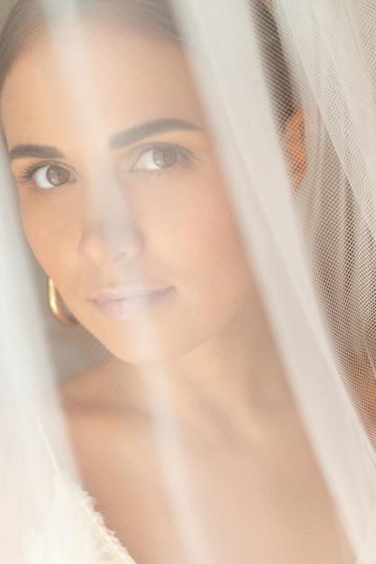 Porträt der schönen dame unter weißem schleier Premium Fotos