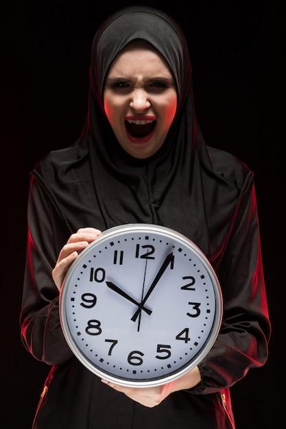 Porträt der schönen ernsten erschrockenen erschrockenen jungen moslemischen frau, die das schwarze hijab hält uhr trägt Premium Fotos