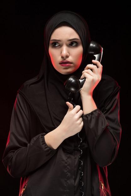 Porträt der schönen ernsten erschrockenen erschrockenen jungen moslemischen frau, die schwarzes hijab ruft um hilfe auf schwarzem trägt Premium Fotos