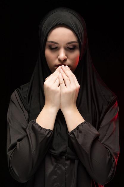 Porträt der schönen ernsten jungen moslemischen frau, die schwarzes hijab mit den händen nahe ihrem gesicht als betendem konzept auf schwarzem trägt Premium Fotos