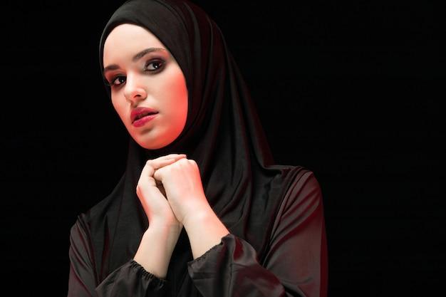 Porträt der schönen ernsten jungen moslemischen frau, die schwarzes hijab mit hand an hand als betendes konzept auf schwarzem trägt Premium Fotos