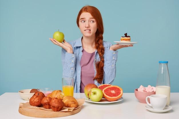 Porträt der schönen fitnessfrau in der sportkleidung, die versucht, zwischen gesundem und ungesundem essen zu wählen Kostenlose Fotos