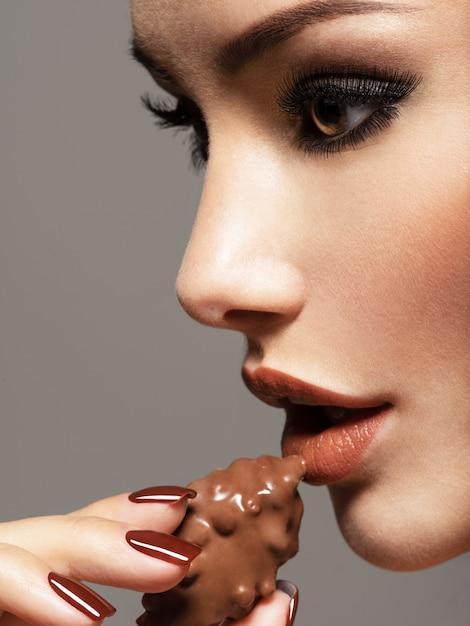 Porträt der schönen frau des glamours hält und isst praline. foto im braunen farbstil Kostenlose Fotos