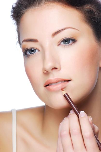 Porträt der schönen frau, die lippenstift unter verwendung des lippen-concealer-pinsels anwendet Kostenlose Fotos