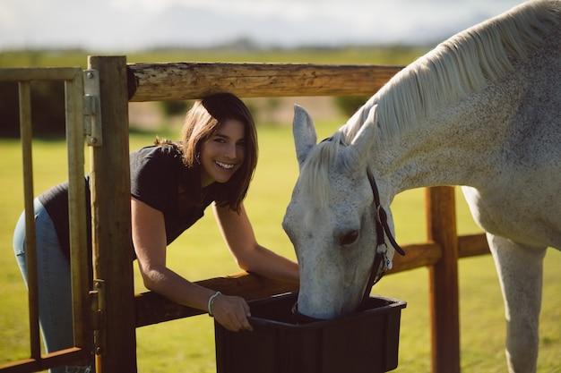 Porträt der schönen frau, die pferd im ackerland füttert Kostenlose Fotos