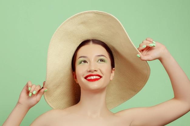 Porträt der schönen frau mit hellem make-up und hut auf grünem studio Kostenlose Fotos