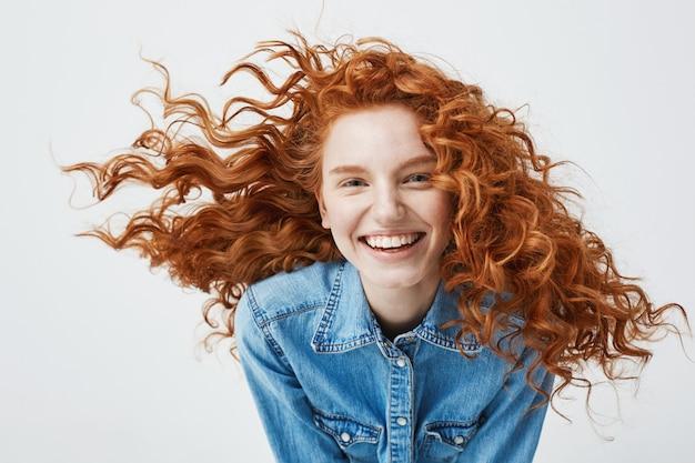 Porträt der schönen fröhlichen rothaarigen frau mit dem fliegenden lockigen haar lächelnd lachend. Kostenlose Fotos