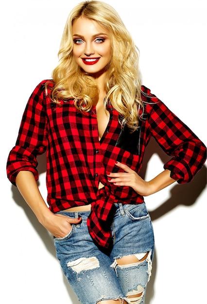 Porträt der schönen glücklichen niedlichen lächelnden blonden frau böses mädchen im lässigen roten hipster winter karierten flanellhemd und blue jeans kleidung mit roten lippen Kostenlose Fotos