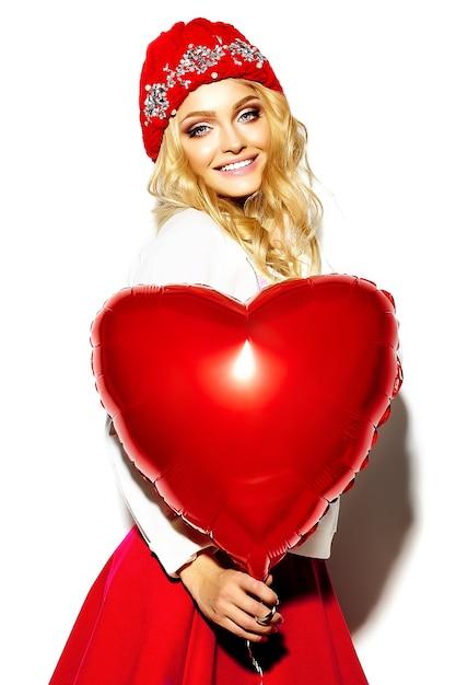 Porträt der schönen glücklichen süßen niedlichen lächelnden blonden frau in lässigen hipster-kleidern, im rosa rock und in der warmen wintermütze mit rotem herzballon in den händen Kostenlose Fotos