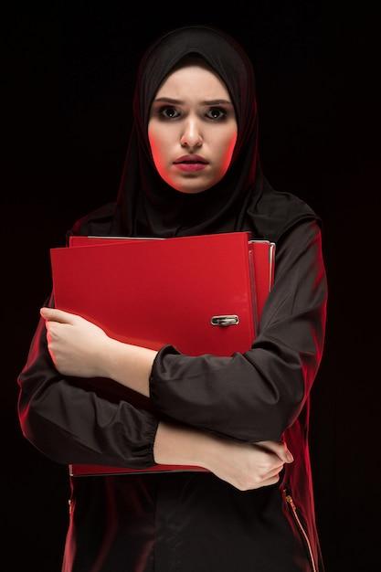 Porträt der schönen hoffnungslosen erschrockenen erschrockenen jungen moslemischen frau, die das schwarze hijab hält ordner als das halten des geheimen konzeptschwarzen trägt Premium Fotos