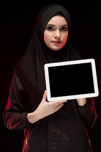 Porträt der schönen intelligenten jungen moslemischen frau, die das schwarze hijab hält tablette in ihren händen als bildungskonzept trägt Premium Fotos