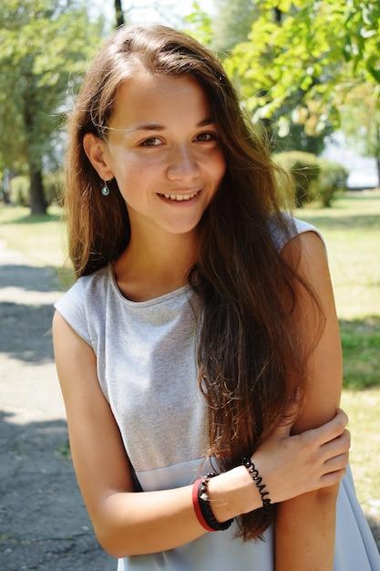 Porträt der schönen jugendlichen in der blauen bluse, gegen grün des sommerparkspiels mit ihrem haar. Premium Fotos