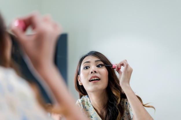 Porträt der schönen jungen asiatin, die make-up anwendet Premium Fotos