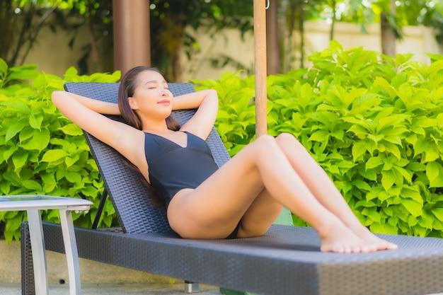 Porträt der schönen jungen asiatischen frau, die sich um den außenpool im hotelresort entspannt Kostenlose Fotos