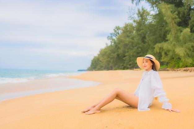 Porträt der schönen jungen asiatischen frau, die sich um strandmeerozean im reiseurlaub entspannt Kostenlose Fotos