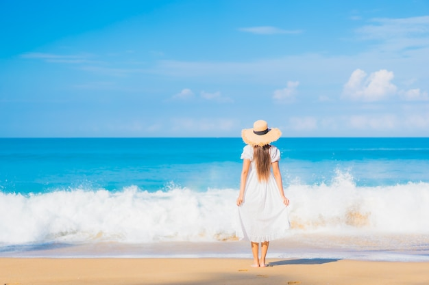 Porträt der schönen jungen asiatischen frau, die um strand mit weißen wolken auf blauem himmel im reiseurlaub entspannt Kostenlose Fotos