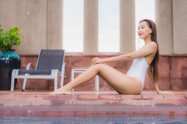 Porträt der schönen jungen asiatischen frau entspannt sich im pool Kostenlose Fotos