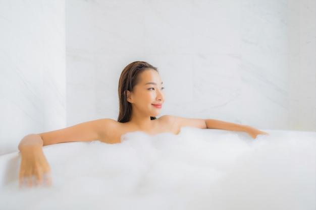 Porträt der schönen jungen asiatischen frau entspannt sich in der badewanne Kostenlose Fotos