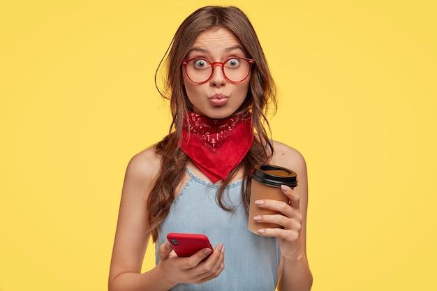 Porträt der schönen jungen brünette mit brille, die gegen die gelbe wand aufwirft Kostenlose Fotos