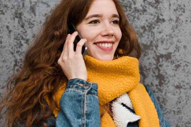 Porträt der schönen jungen frau, die am telefon spricht Kostenlose Fotos