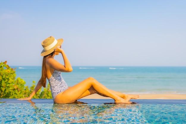 Porträt der schönen jungen frau, die auf dem pool entspannt Kostenlose Fotos