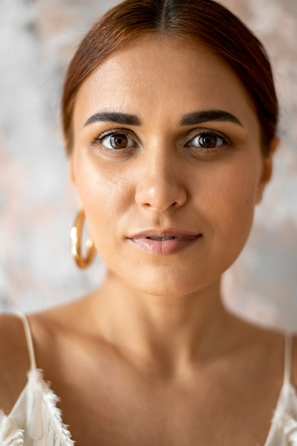 Porträt der schönen jungen frau, die einen ohrring nah oben trägt Premium Fotos