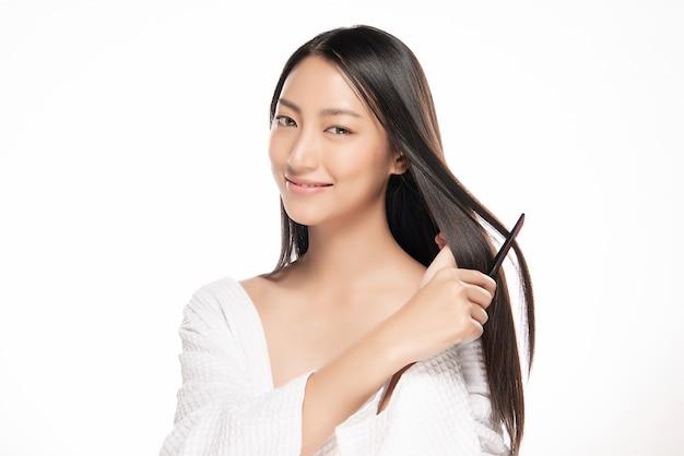 Porträt der schönen jungen frau, die ihr haar kämmt. Premium Fotos