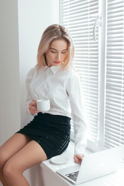 Porträt der schönen jungen frau, die im büro arbeitet. Premium Fotos