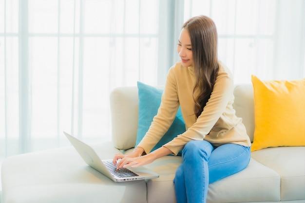 Porträt der schönen jungen frau, die laptop auf sofa im wohnzimmer verwendet Kostenlose Fotos
