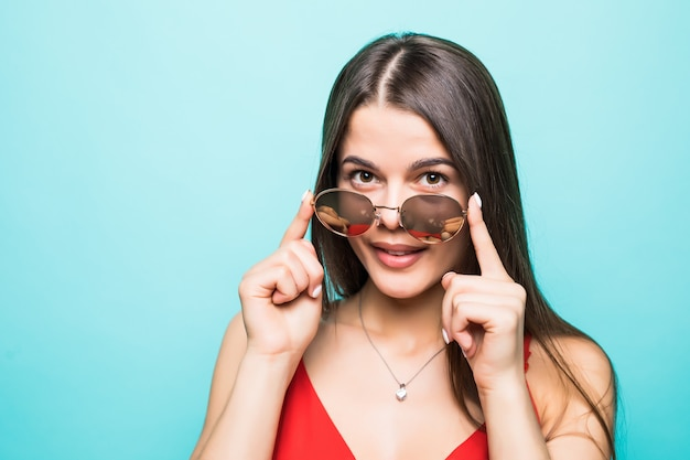 Porträt der schönen jungen frau im roten kleid an der blauen wand Kostenlose Fotos
