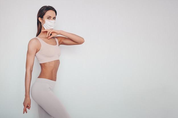 Porträt der schönen jungen frau in der sportkleidung, die schutzmaske trägt Premium Fotos