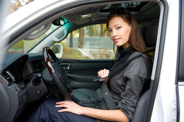 Porträt der schönen jungen frau legt einen sicherheitsgurt im auto an Kostenlose Fotos