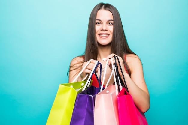 Porträt der schönen jungen frau mit einkaufstüten an der blauen wand Kostenlose Fotos
