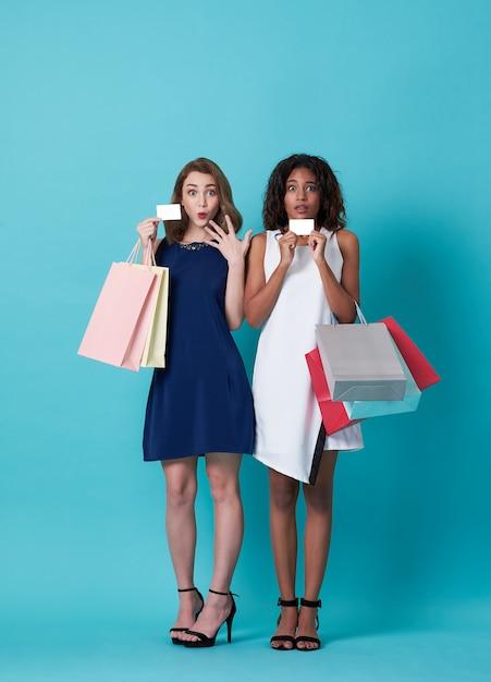 Porträt der schönen jungen frau zwei, welche die kreditkarte und einkaufstasche lokalisiert über blauem hintergrund zeigt. Premium Fotos