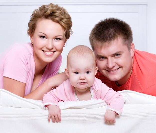 Porträt der schönen jungen glücklichen familie, die zu hause im bett liegt Kostenlose Fotos