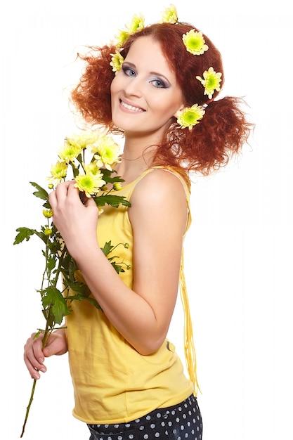 Porträt der schönen lächelnden rothaarigen ingwerfrau im gelben stoff, der gelbe blumen und blumen im haar lokalisiert auf weiß hält Kostenlose Fotos