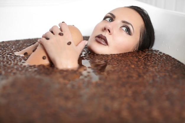 Porträt der schönen modefrau im whirlpool mit kaffee. körperpflege. helles make-up Kostenlose Fotos