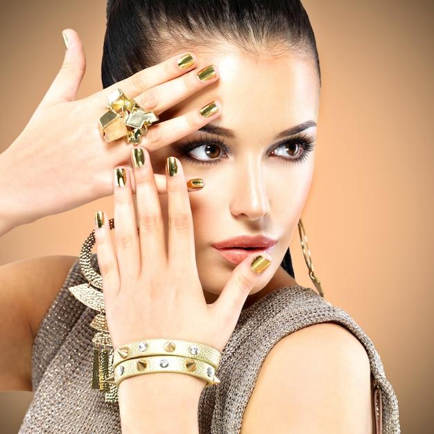 Porträt der schönen modefrau mit schwarzem make-up und goldener maniküre Kostenlose Fotos