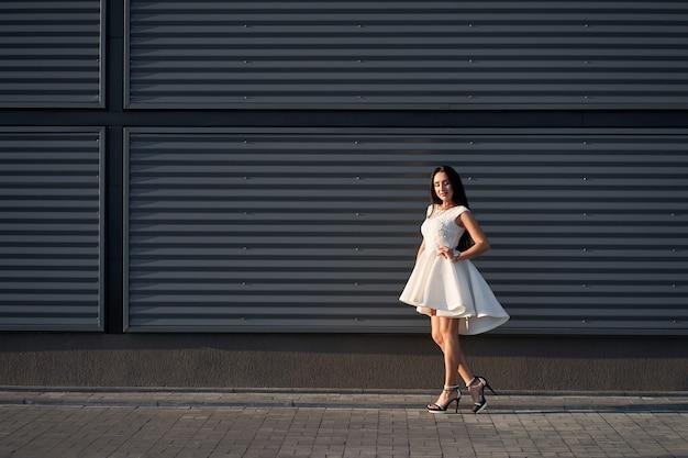 Porträt der schönen modisch gekleideten brünetten frau, die weißes stilvolles elegantes kleid aufwirft Premium Fotos