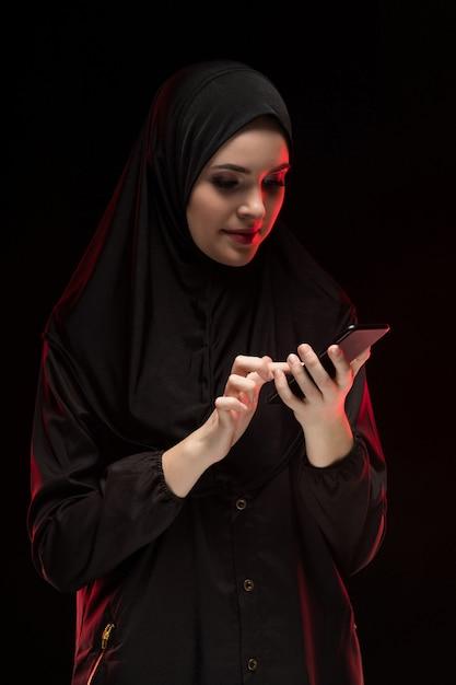 Porträt der schönen positiven freundlichen jungen moslemischen frau, die das schwarze hijab hält handy trägt Premium Fotos