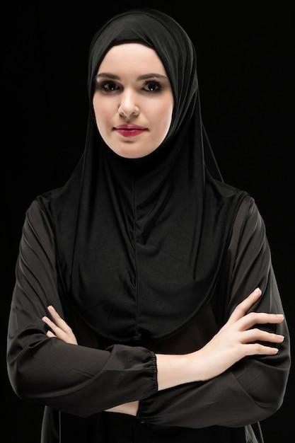 Porträt der schönen positiven jungen moslemischen frau, die schwarzes hijab als konservatives modekonzept mit den gekreuzten armen lächeln auf schwarzem hintergrund trägt Premium Fotos