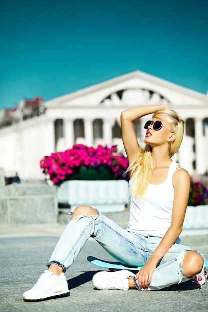 Porträt der schönen stilvollen jungen frau mit skateboard Kostenlose Fotos
