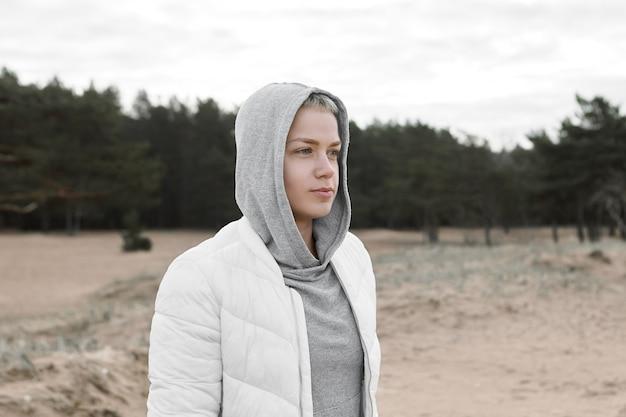 Porträt der schönen stilvollen jungen kaukasischen frauenhaube und der weißen jacke, die auf verlassenem sandstrand während der ferien auf see gehen. konzept für freizeit, entspannung, aktivität, menschen und lebensstil Kostenlose Fotos
