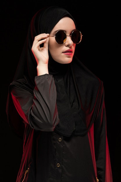 Porträt der schönen stilvollen jungen moslemischen frau, die schwarzes hijab und sonnenbrille als modernes ostmodekonzept aufwirft auf schwarzem hintergrund trägt Premium Fotos
