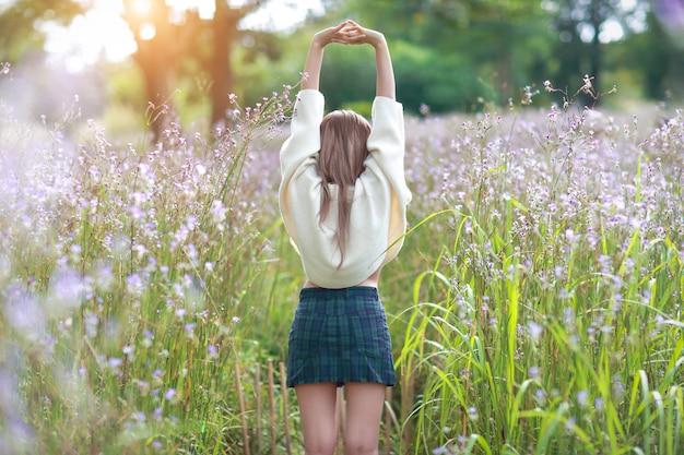 Porträt der schönheit eine glückliche zeit habend und unter blume naga-mit haube feld in der natur genießend Premium Fotos