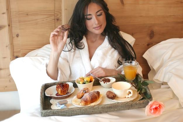 Porträt der schönheit frühstück auf dem bett essend Premium Fotos