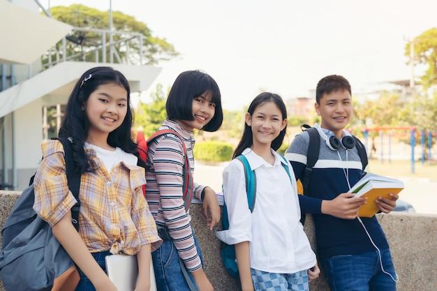 Porträt der schule scherzt mit dem lächelnden stehen der rucksäcke in der volksschulehalle Premium Fotos