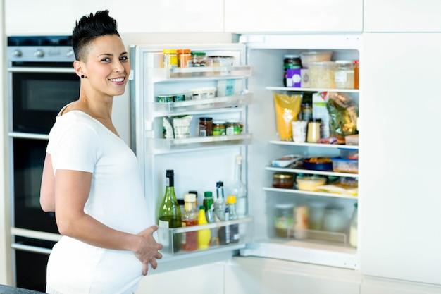 Porträt der schwangeren frau lächelnd beim suchen nach lebensmittel im kühlschrank Premium Fotos