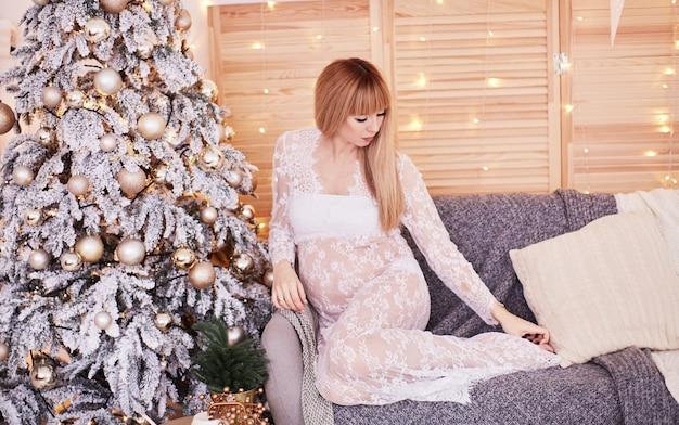 Porträt der schwangeren frau, vibes des neuen jahres. bezaubernde blondine, die frau erwartet, sitzt Kostenlose Fotos